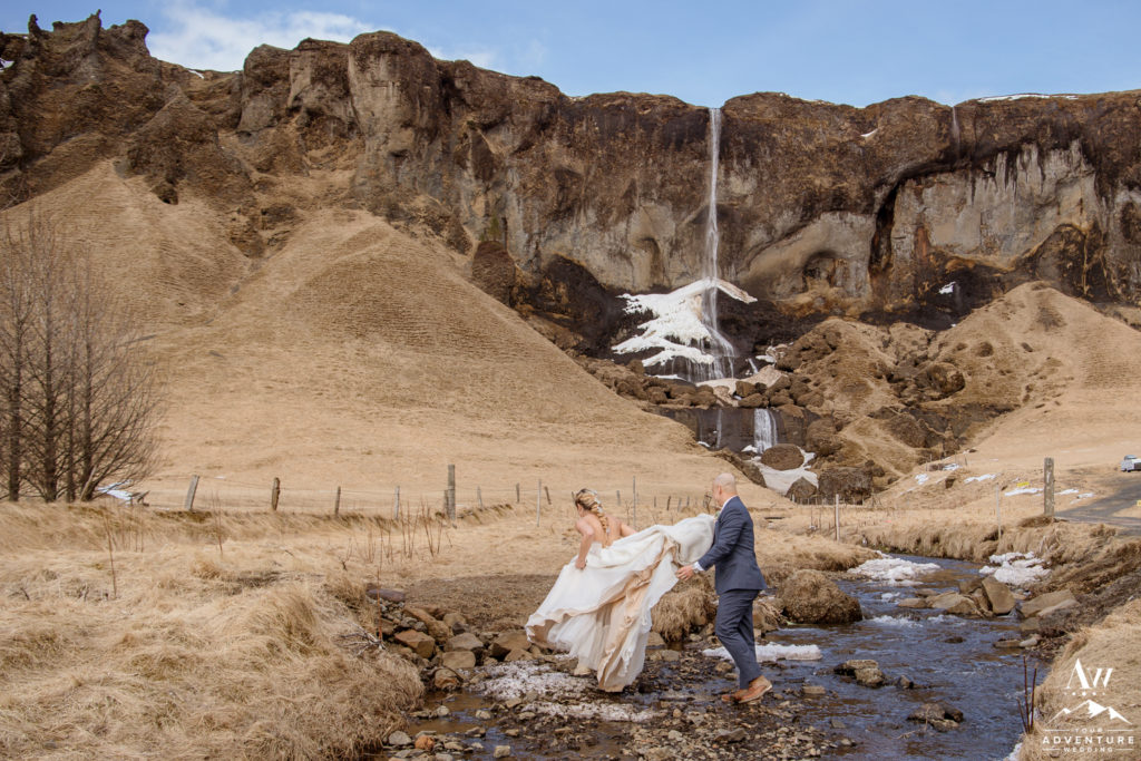 Bride Jumping over a river on Iceland adventure wedding day