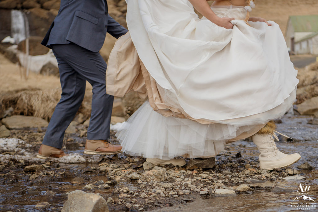 Couple crossing a river during Iceland adventure wedding