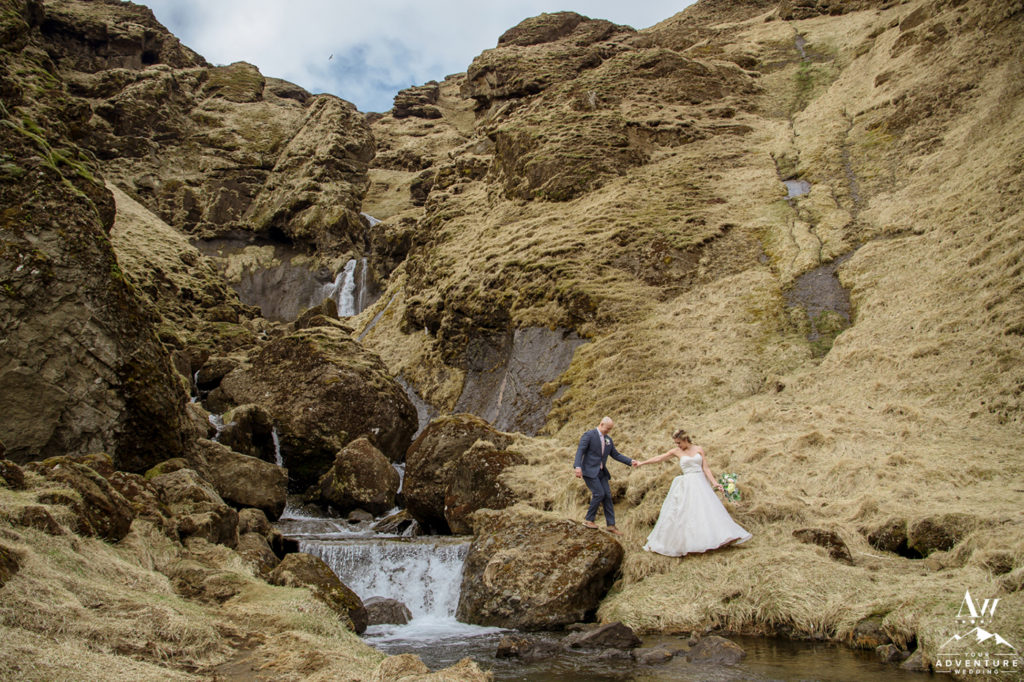 Bride leading her groom down from a private waterfall