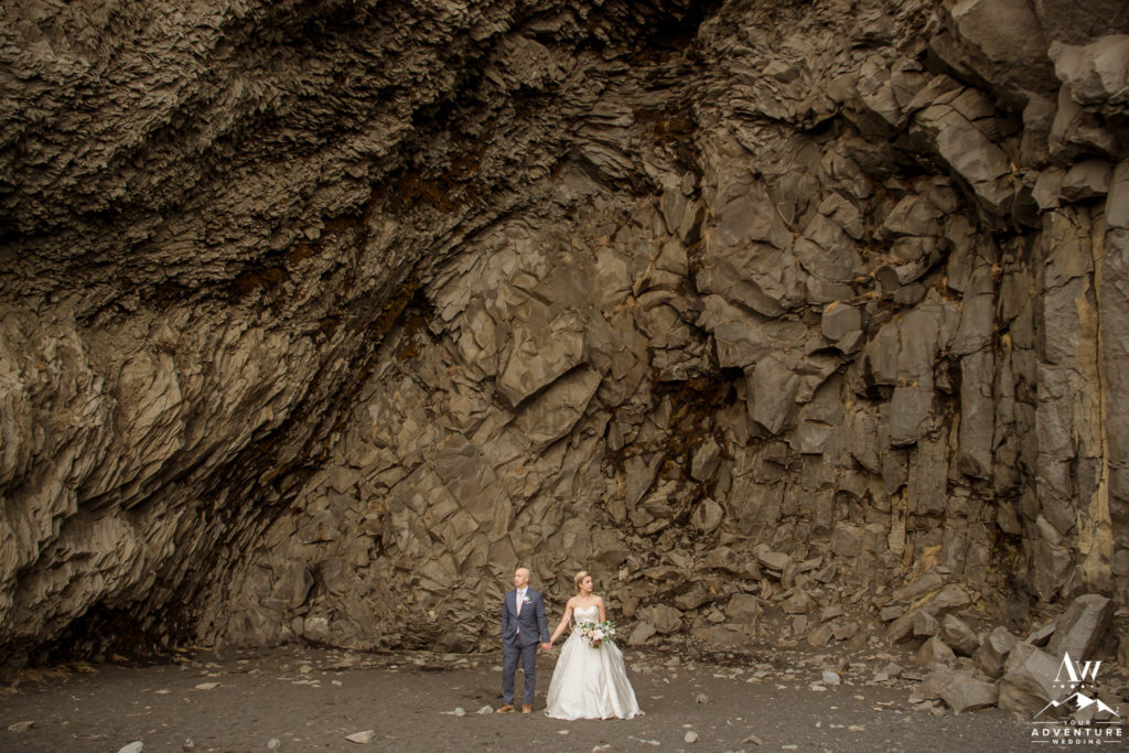 Iceland wedding couple standing in the cave opening in Vik
