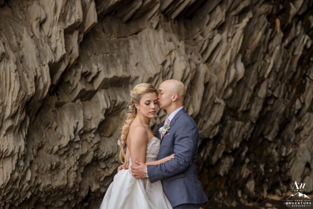 Groom kissing his bride in front of a cave in Iceland