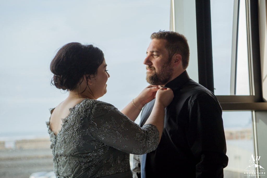 Bride helping dress her Iceland wedding groom
