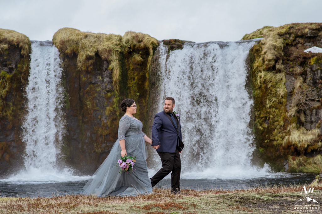 Iceland Wedding Couple walking in front of a waterfall