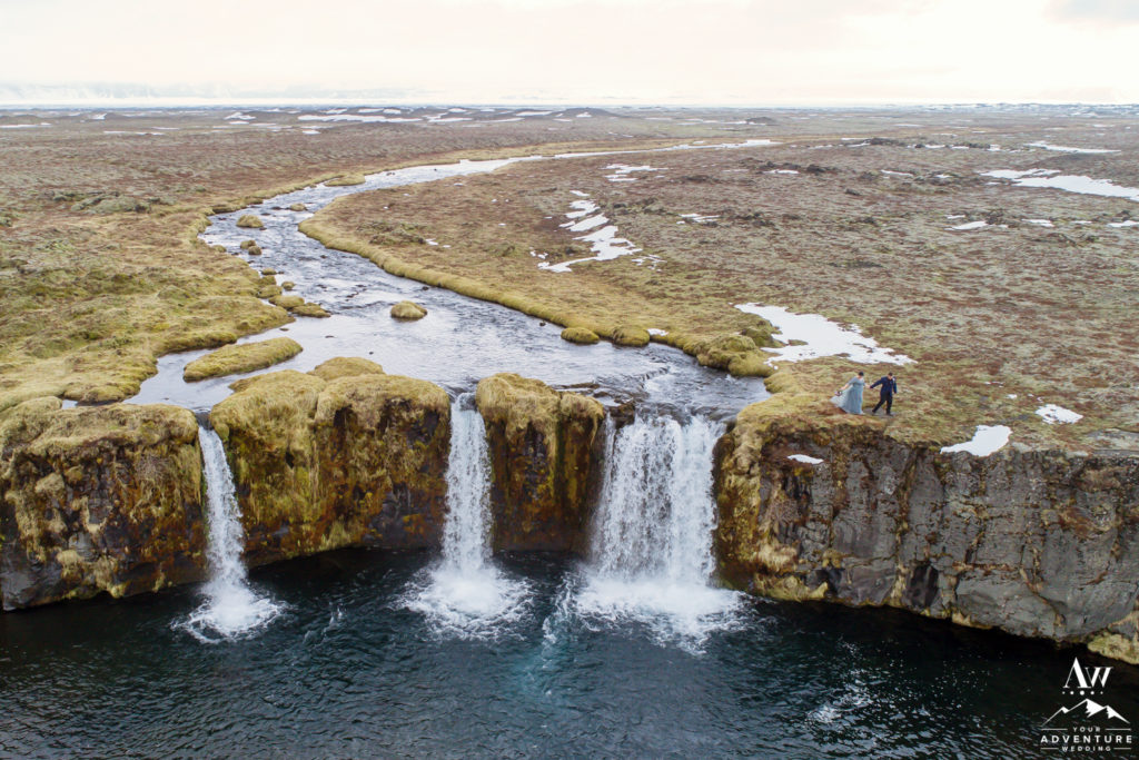 Couple Standing on top of a private waterfall in Iceland
