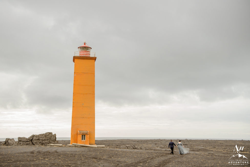 Iceland wedding couple walking on black sand beach with orange lighthouse nearby