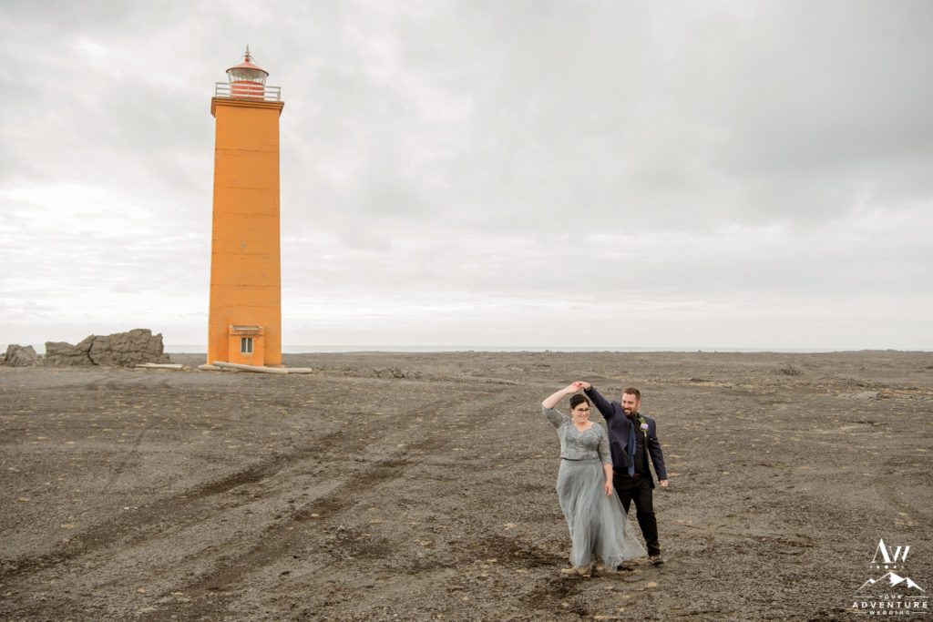 Iceland wedding couple dancing in front of a lighthouse