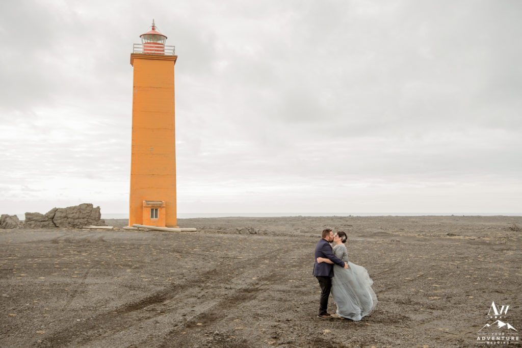 Iceland Wedding Couple Kissing in front of a orange lighthouse