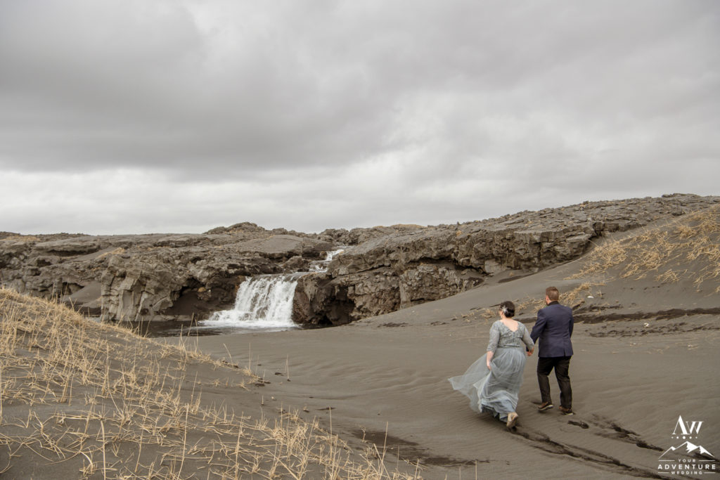 Iceland Elopement Couple Walking towards black beach waterfall