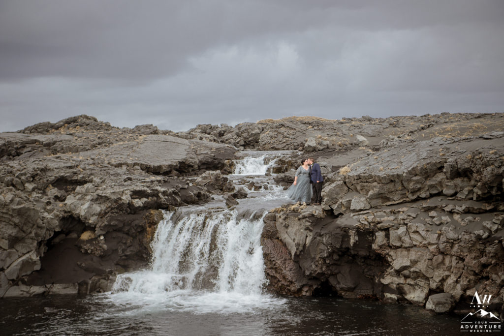 Iceland Elopement Couple standing atop of lava rock waterfall
