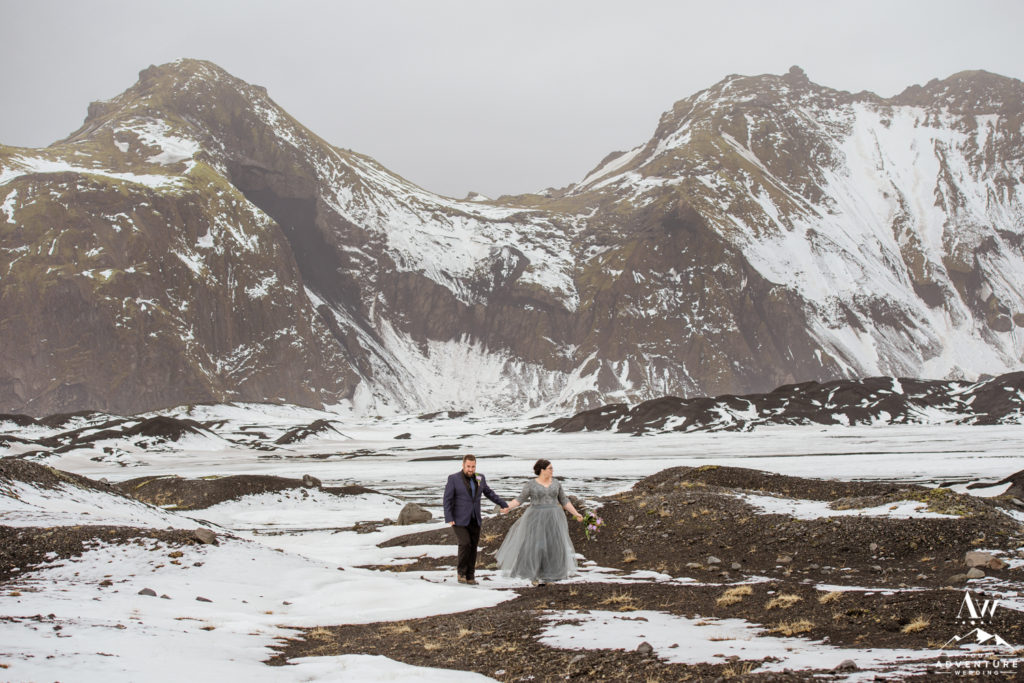 Couple in front of a snowy mountain during April wedding in Iceland