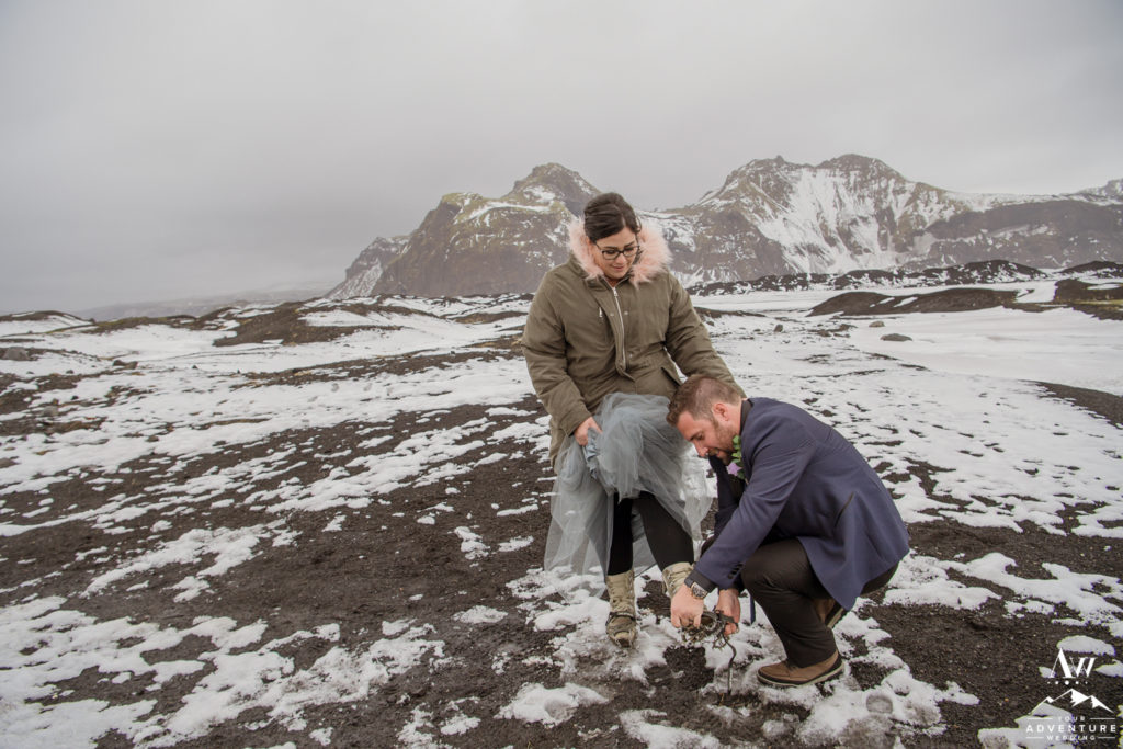 Groom helping his bride with crampons during Iceland Elopement