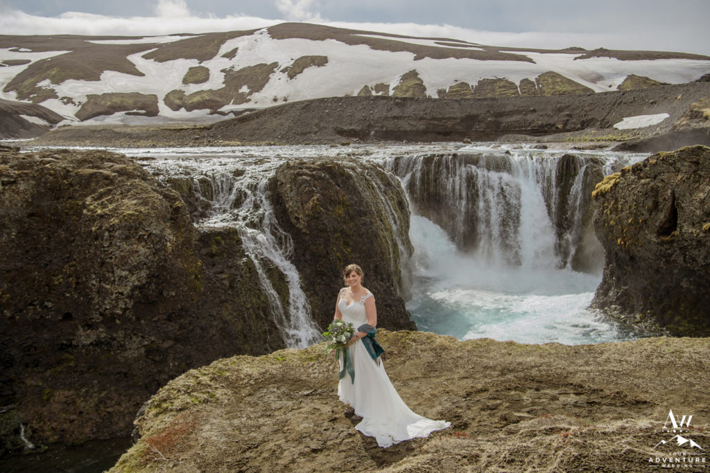 Bride standing in front of a secret highland waterfall