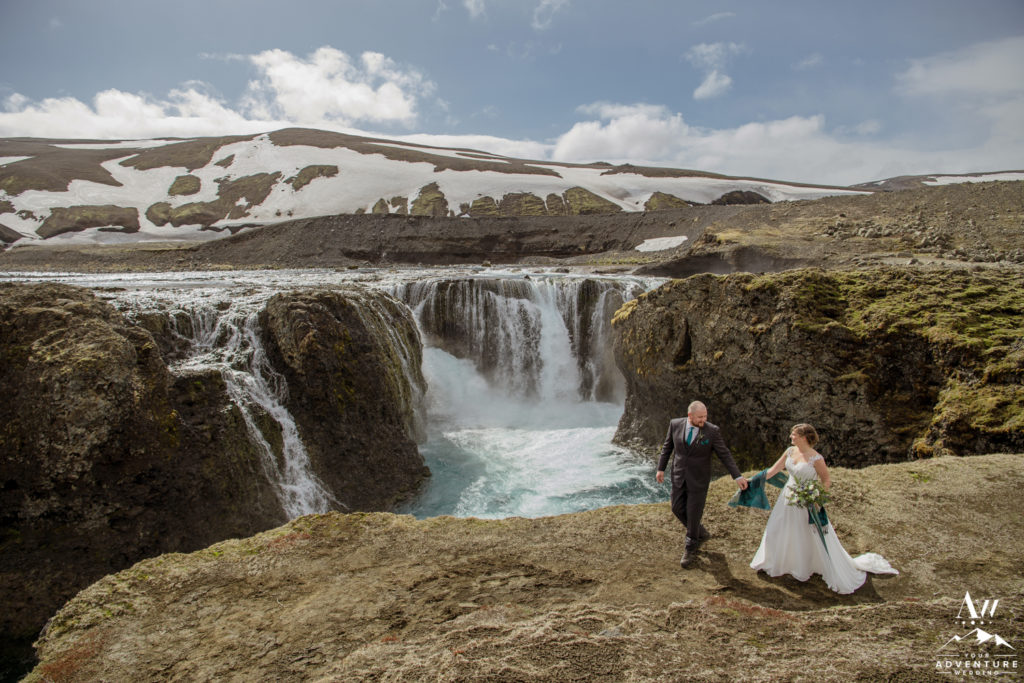 Couple walking in front of an Icelandic Highland Waterfall
