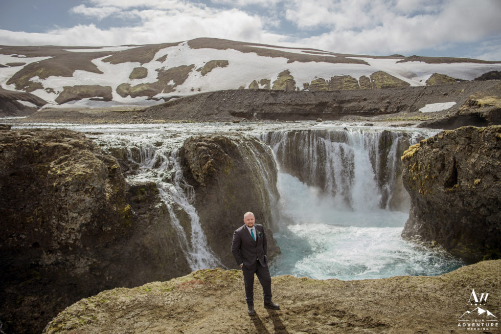 Groom standing in front of a Iceland Highland Waterfall