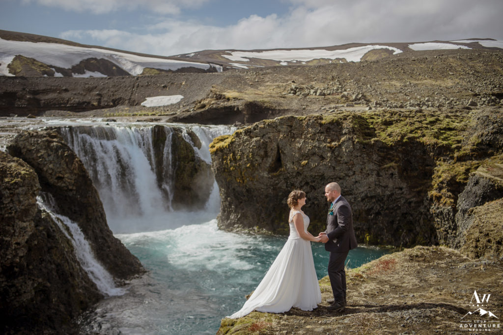 Iceland Elopement Couple Standing holding hands in front of a waterfall