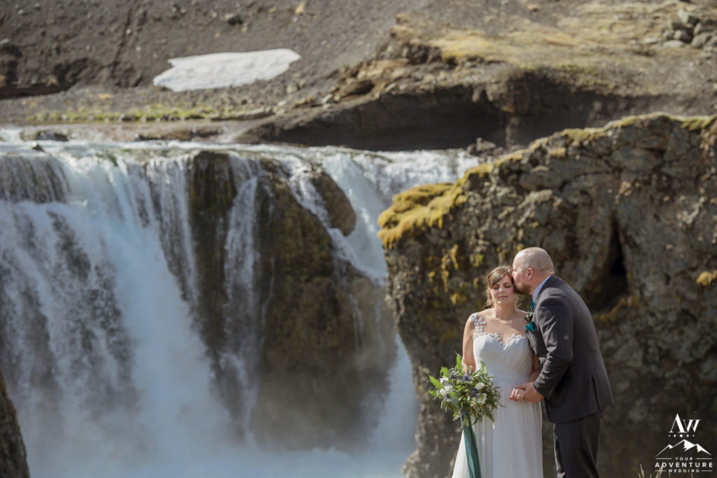 Groom kisses his bride in front of a highland waterfall in Iceland