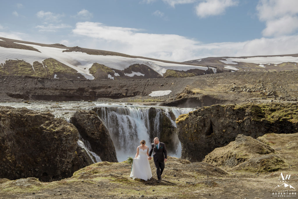 Couple Walking in front of a waterfall in Iceland