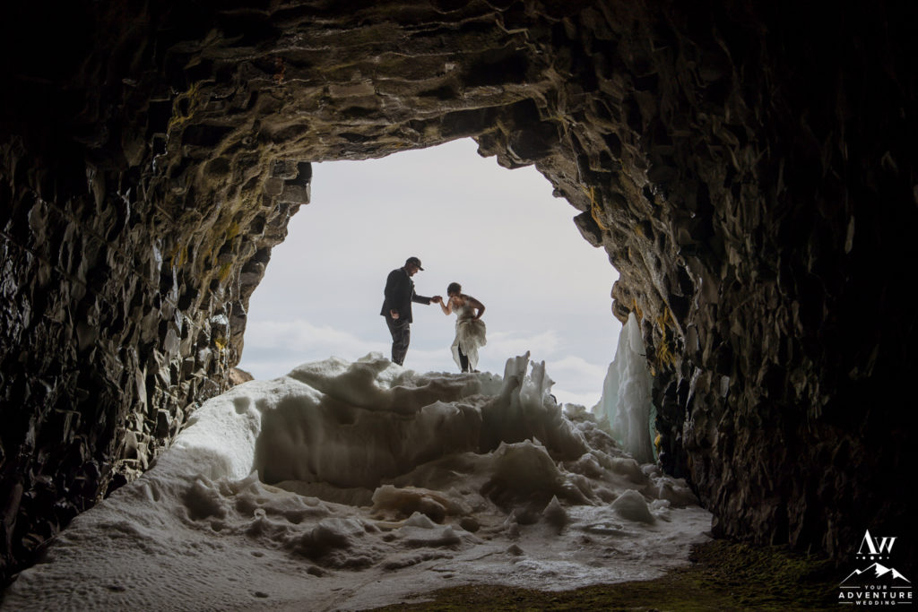 Groom helping his bride into a cave
