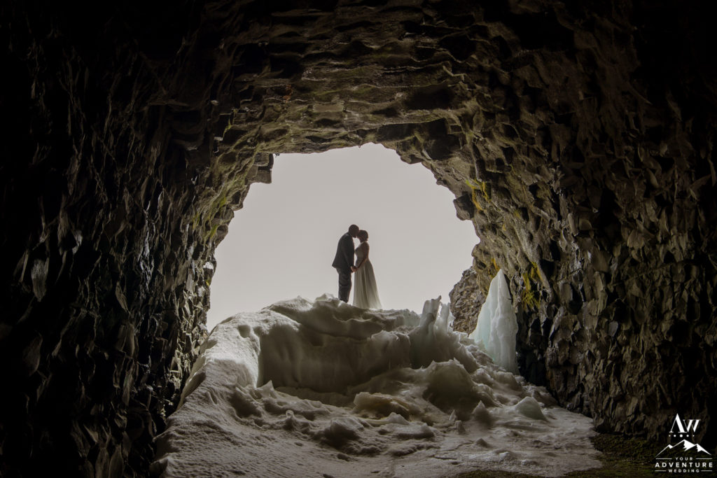 Iceland Wedding Couple kissing in front of a Highland Cave