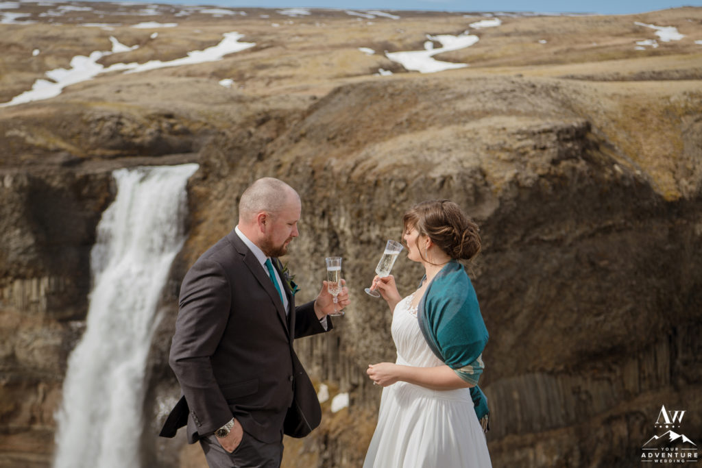 Couple sipping champagne in front of a waterfall