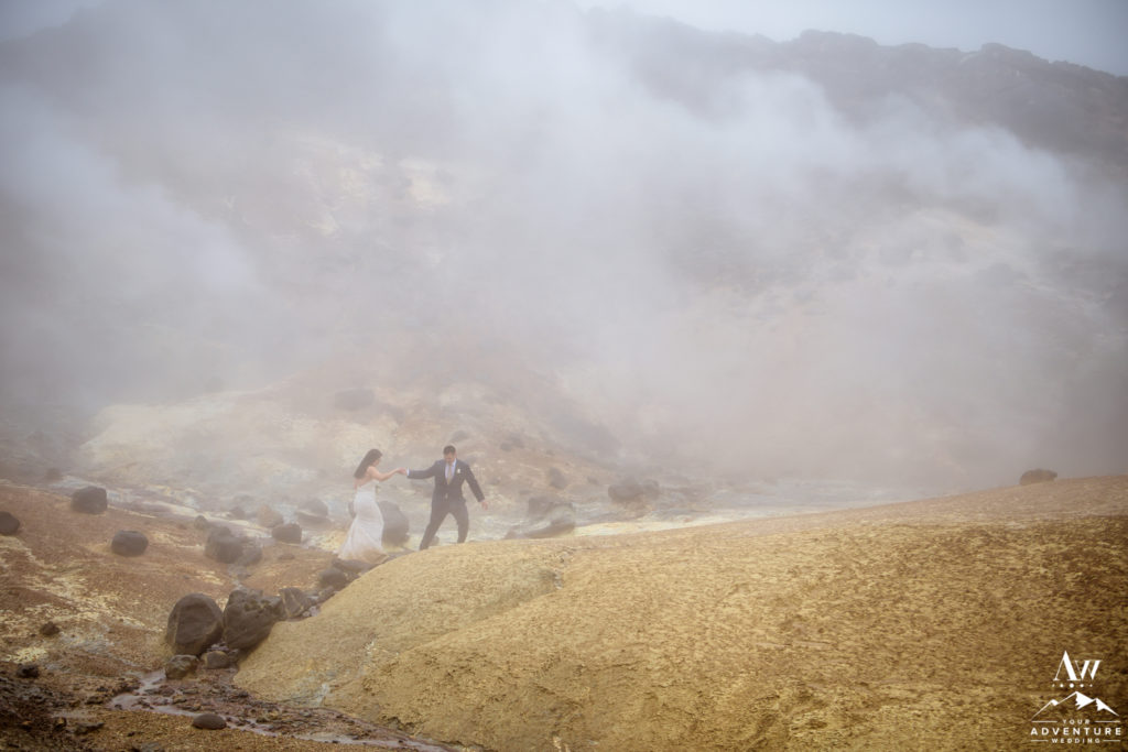 Couple hiking through geothermal area on Iceland wedding day