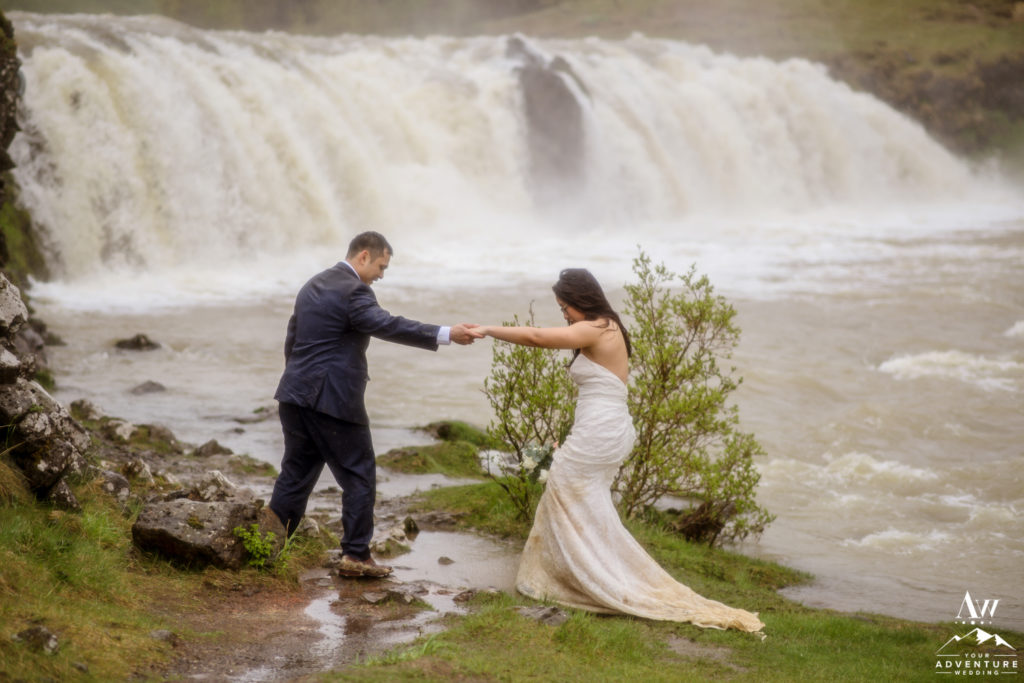 Groom helping his bride across a river