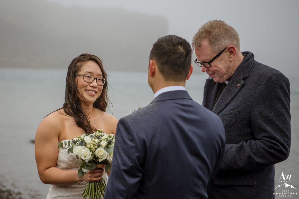 Bride smiling at her Groom during rainy Iceland wedding ceremony