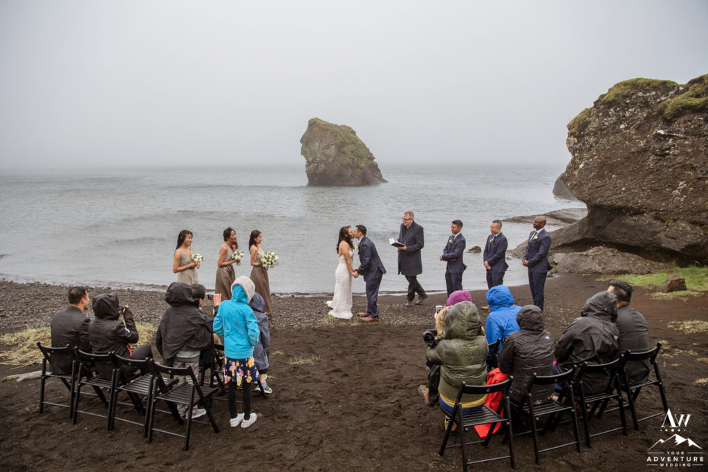 Couple kissing during rainy Iceland wedding day adventure