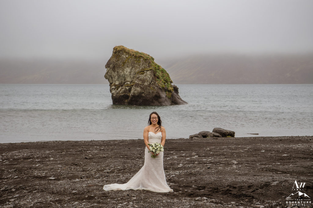 Bride standing on a black beach in the rain in Iceland