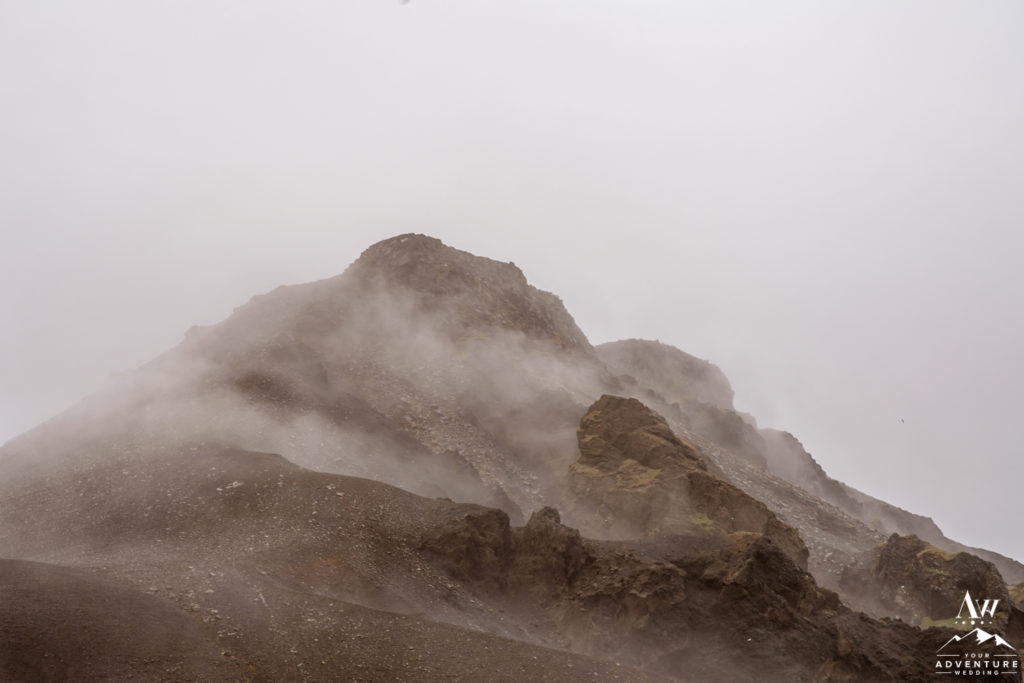 Fog on top of mountains during rainy Iceland wedding day