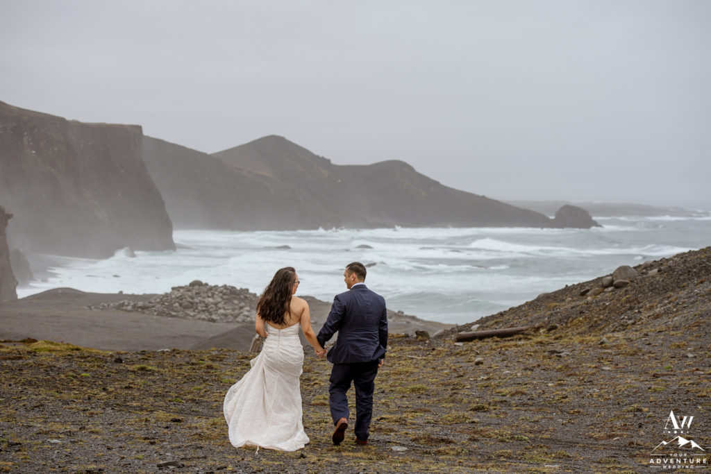 Iceland Wedding Couple walking towards sea cliffs