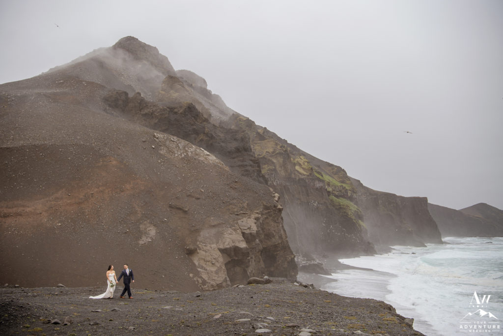 Couple walking in front of cliffs during rainy Iceland adventure wedding