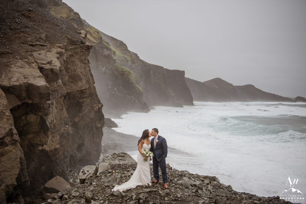 Couple kissing during rainy Iceland wedding day