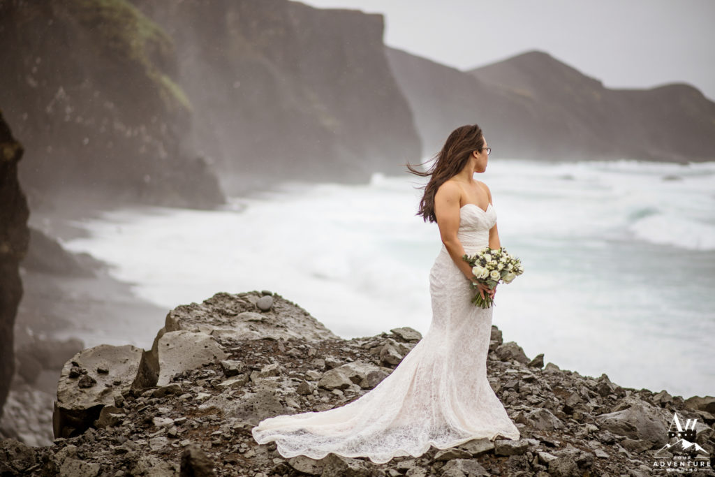 Bride looking out to the sea on rainy Iceland Wedding Day