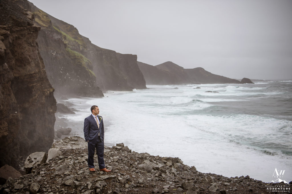 Groom looking out to the sea during rainy Iceland wedding day