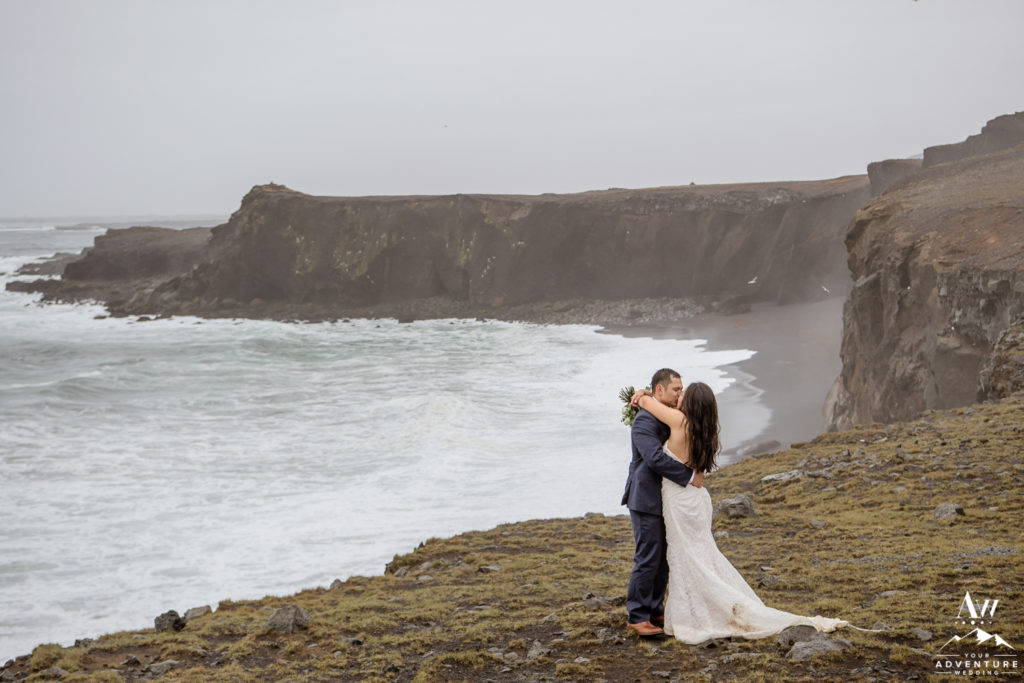 Iceland Wedding Couple kissing in front of sea cliffs
