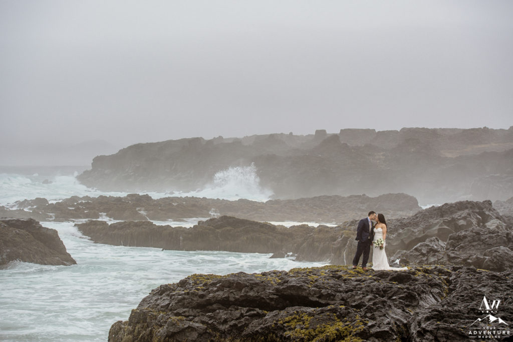 Iceland Wedding Couple kissing on lava rocks near ocean
