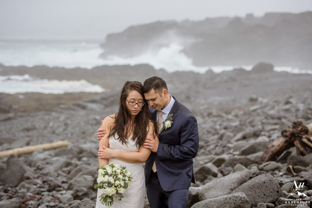 Couple cuddling during rainy Iceland Wedding Day