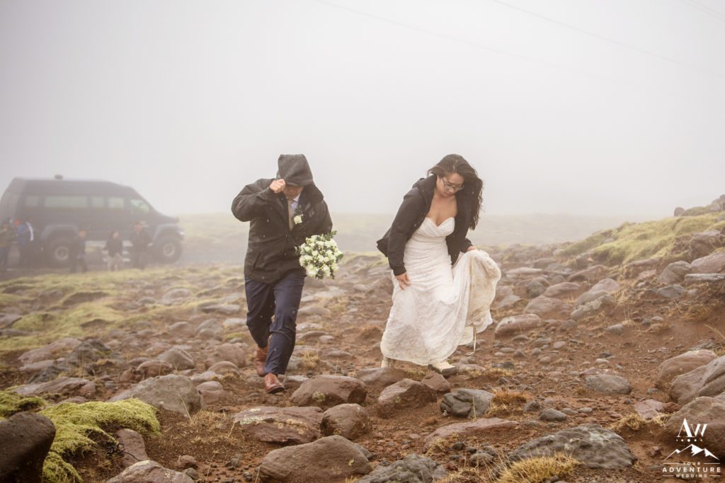 Couple hiking through rain on their adventure wedding in Iceland