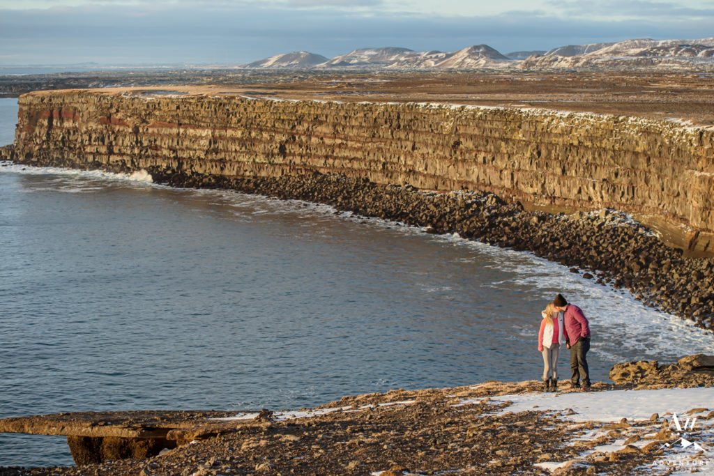 Iceland Proposal Couple Kissing on top of Golden Cliffs