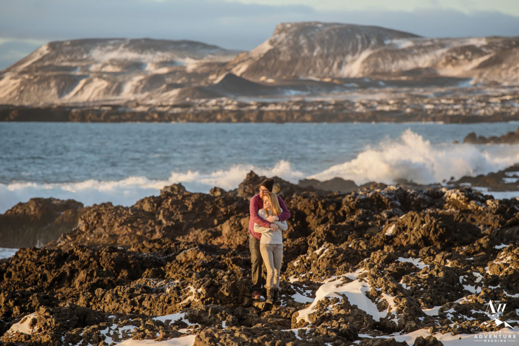 Iceland Engagement Photographer takes couples photo on lava rock beach