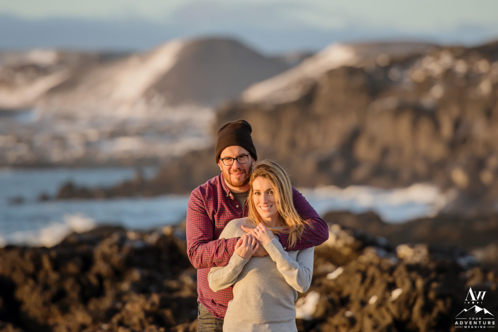 Iceland Engagement Photo with couple looking at the camera and mountains behind