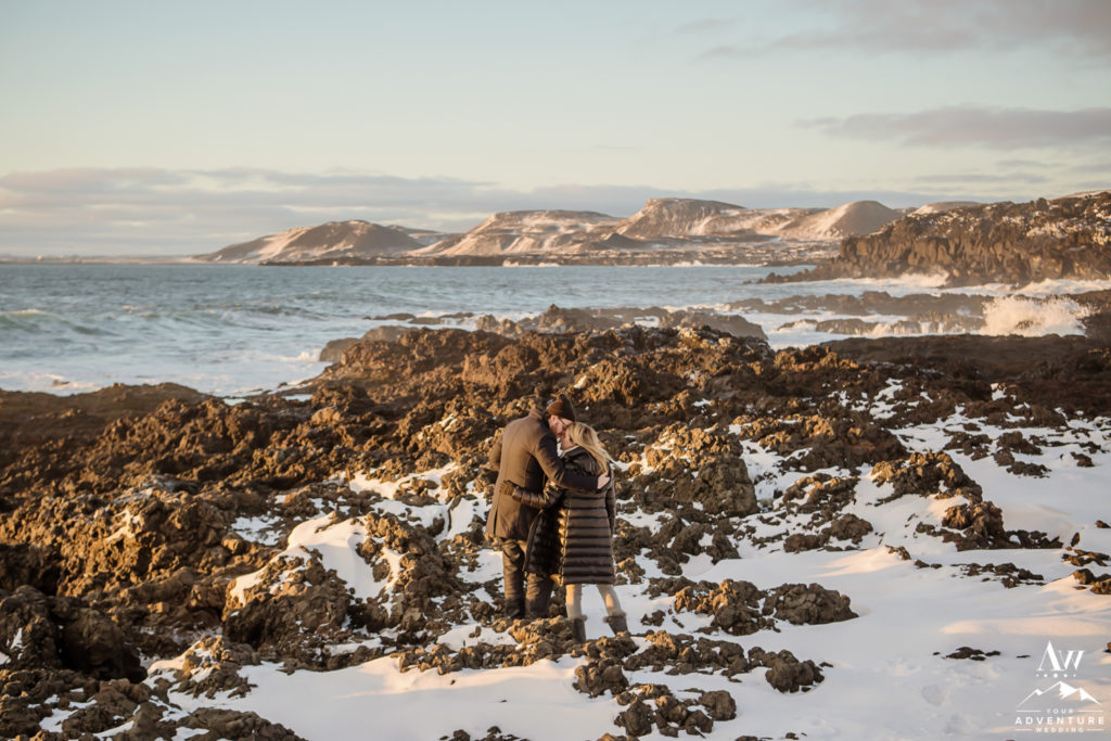 Iceland Engagement Couple kissing on lava rock beach