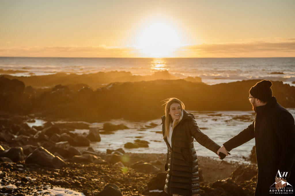 Iceland Engagement Couple walking on lava rock beach at sunset