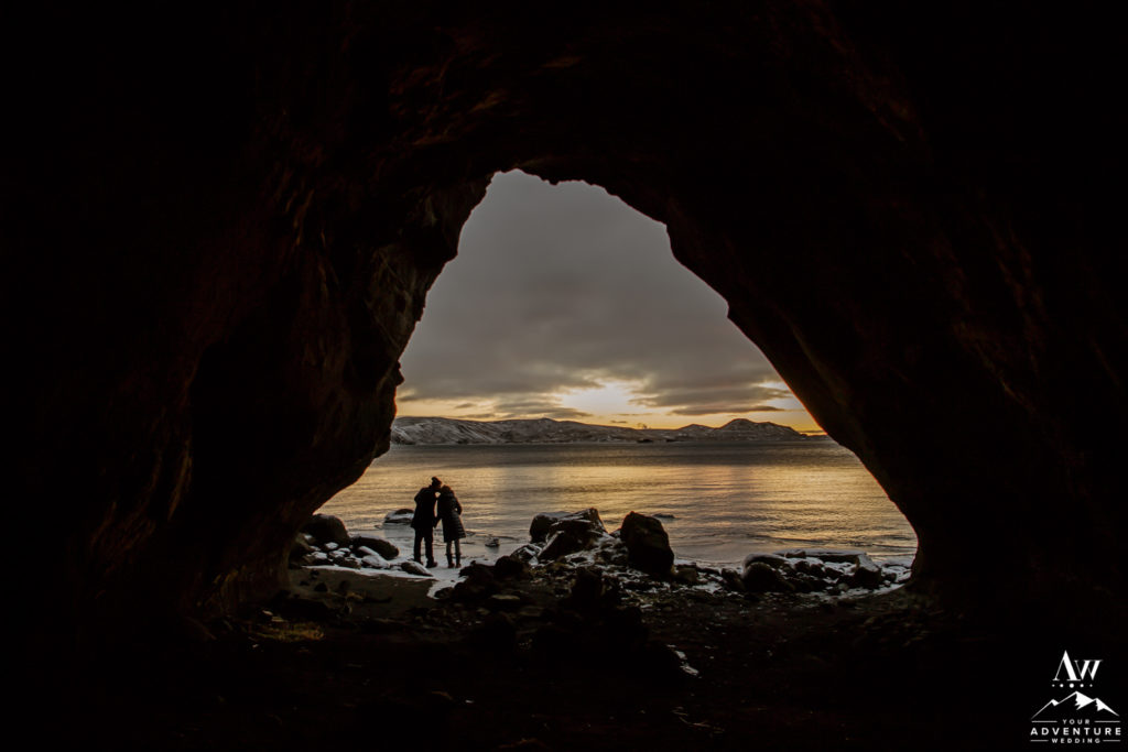 Couple kissing inside of a cave in Iceland at sunset