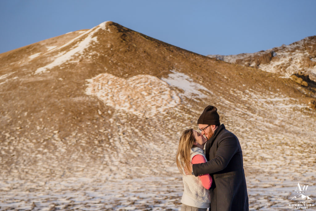 Couple kissing in front of heart shaped mountain in Iceland