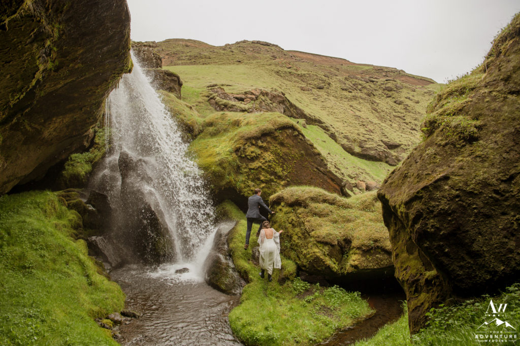 Adventure wedding couple hiking a waterfall on wedding day