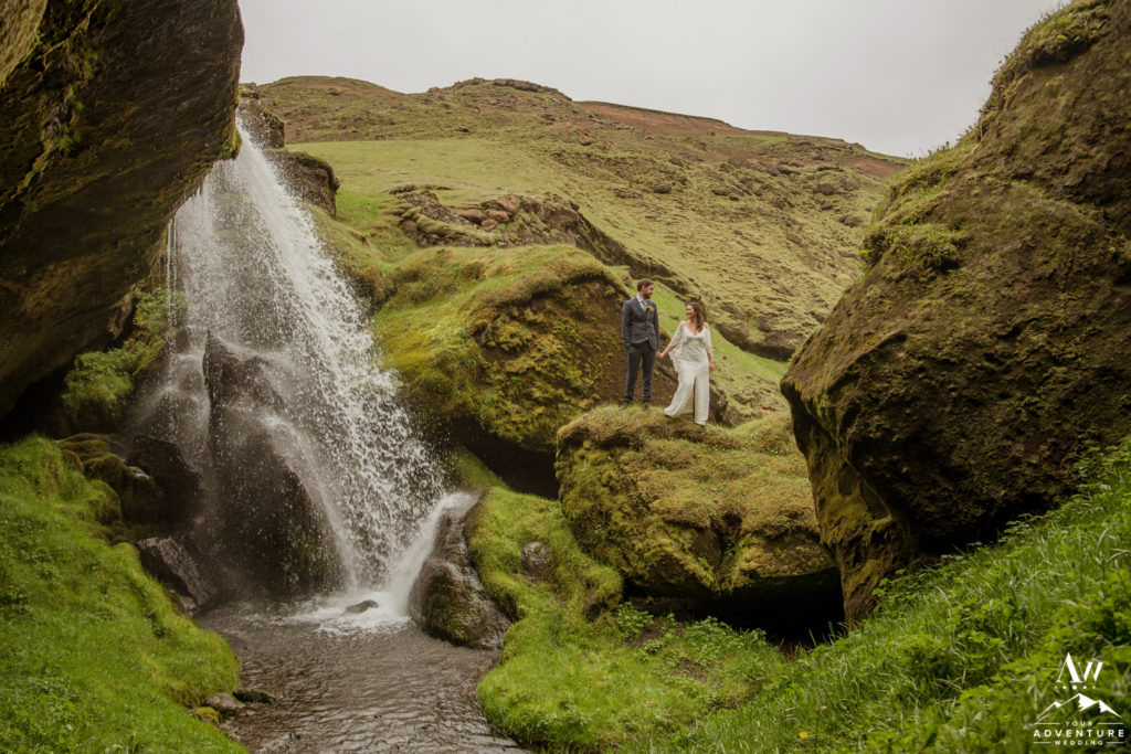 Bride and Groom Standing next to a waterfall in Iceland