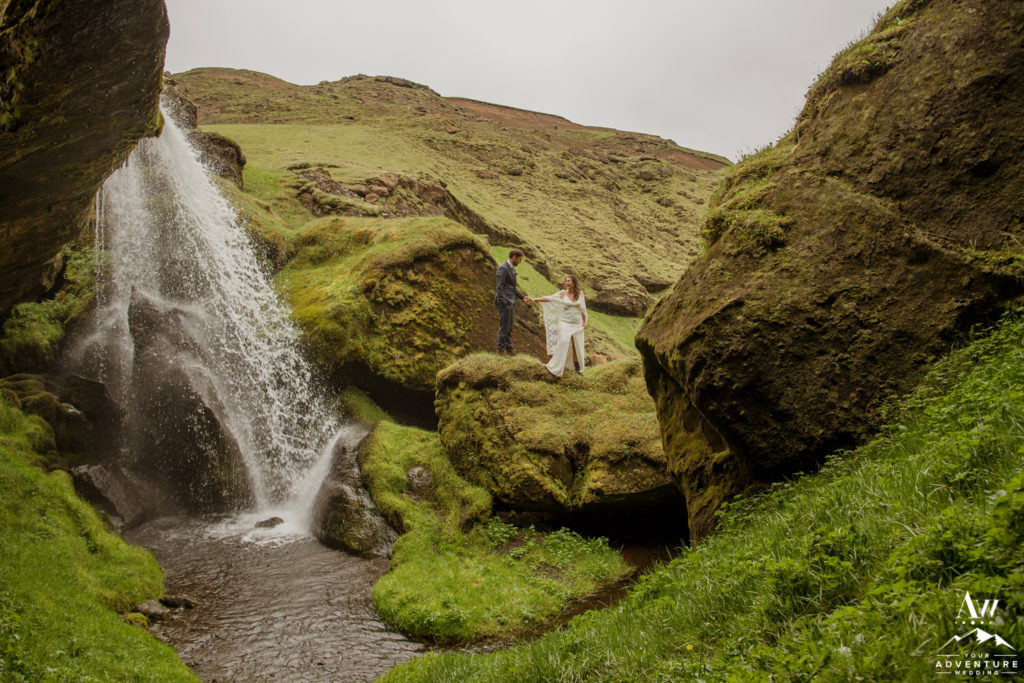 Adventurous Couple Exploring a waterfall on their wedding day in Iceland