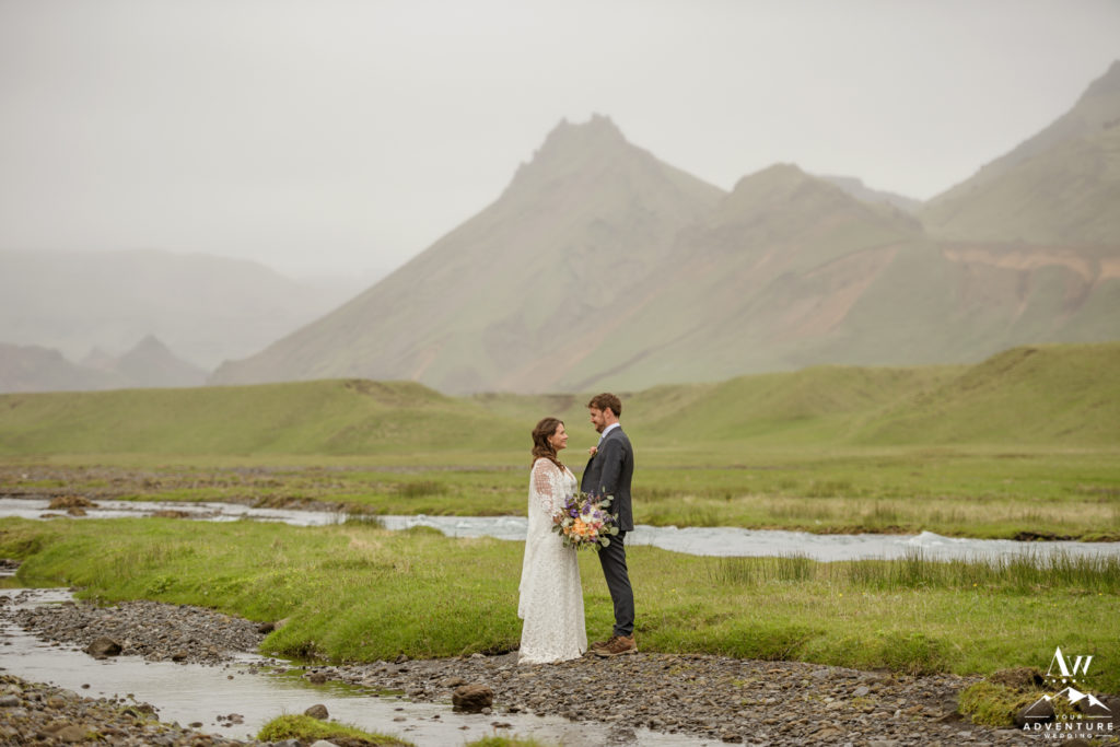 Couple holding hands in front of a mountain in Iceland